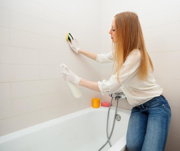 Длинношерстная женщина, чистка плитки с губкой в ванной комнате