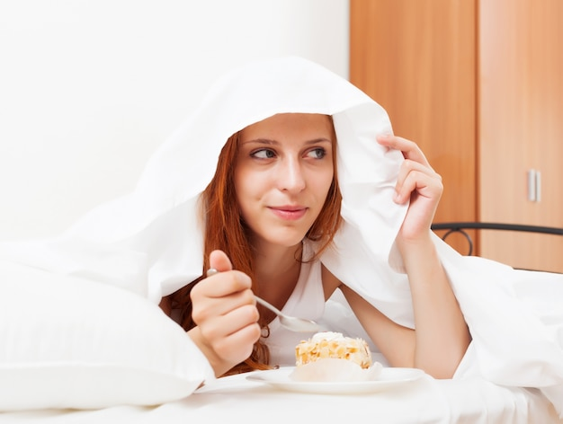 Long-haired woman eating sweets under white sheet