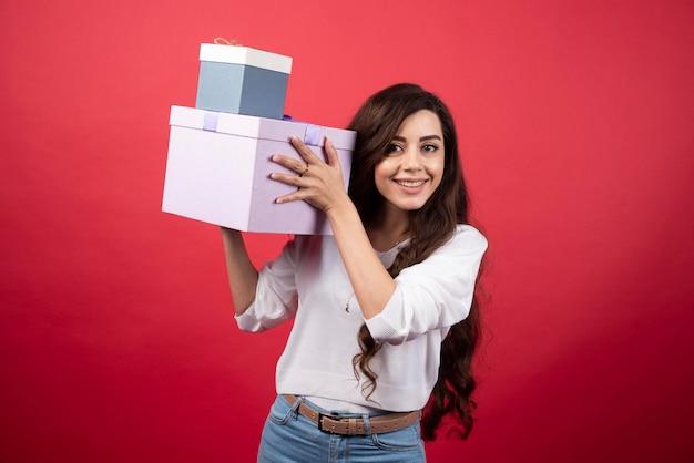 빨간색 바탕에 선물 상자를 들고 장 발 여자. 고품질 사진