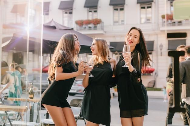Длинноволосая женщина в модном черном боди позирует с целующим выражением лица, глядя на сестру-блондинку