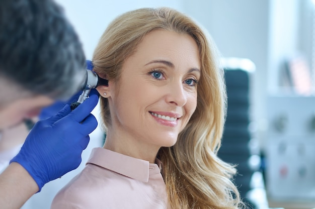 Long-haired woman and otolaryngologist examining ear