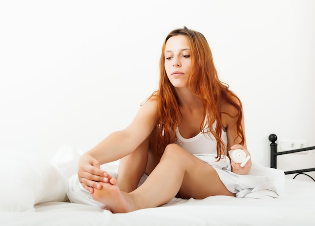 Long-haired  woman putting cream on feet