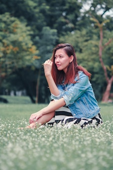 A long haired woman sitting in the lawn