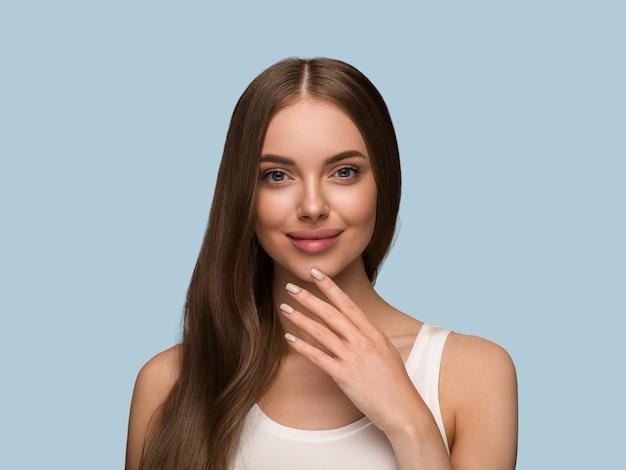 長い巻き毛の美しさの肌の顔の肖像画を持つ長い健康な髪の女性。色の背景青