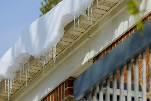 Long icicles on roof house a gutter
