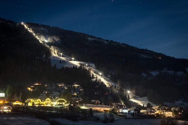 Длинный освещенный горнолыжный склон в австрийских альпах звездной ночью