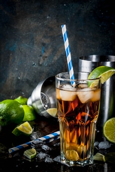 Long island iced tea cocktail with strong alcohol, cola, lime and ice