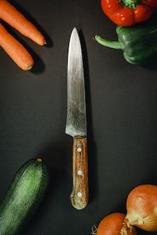Длинный нож в окружении разных овощей