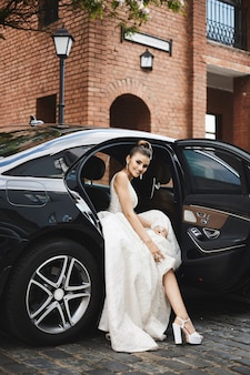 Long legged brunette model girl with bright makeup in a trendy silver dress sits in the luxury car