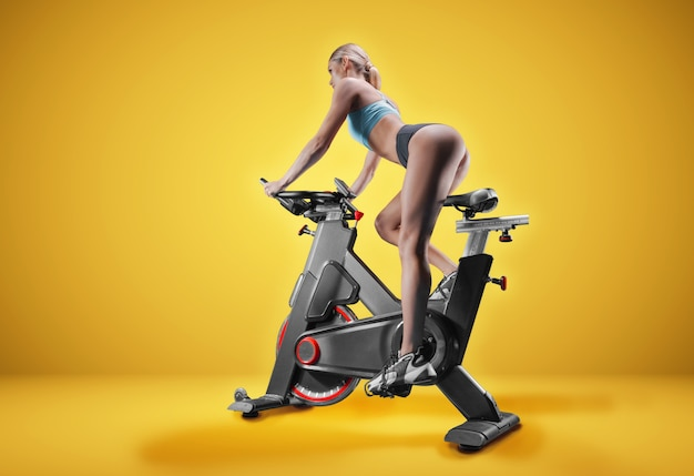 Long-legged girl posing on an exercise bike on a yellow wall.