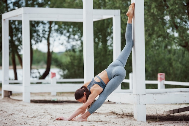 Длинные ноги и приятная растяжка. брюнетка с красивой формой тела в спортивной одежде занимается фитнесом на пляже