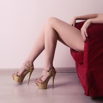 긴 다리와 섹시한 황금빛 하이힐