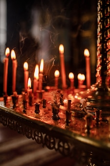 Long lighted candles group in orthodox church. candles background.