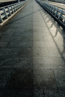 A long marble tile road with white metal railings with a vanishing line on the horizon