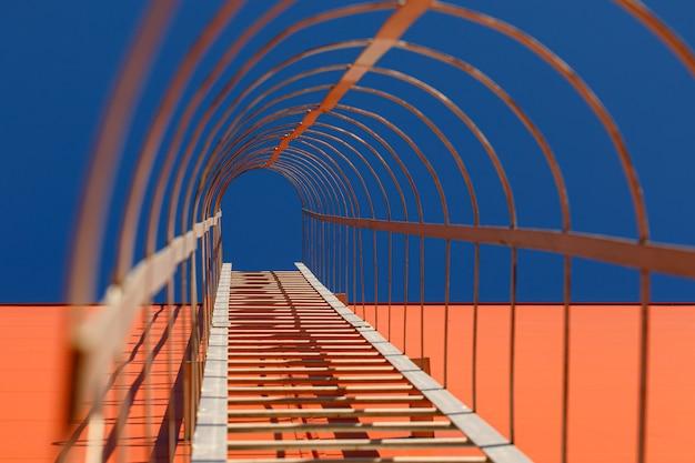 산업 건물의 오렌지 현대 외관에 긴 금속 계단