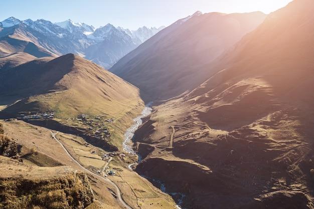 暖かく明るい朝の太陽のパノラマに照らされた山々に対して息を呑むような茶色の急な丘の間を流れる川のある細長い峡谷
