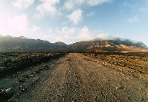 Long off road terrain way road viewed from ground level with mountains and blue cloudy sky