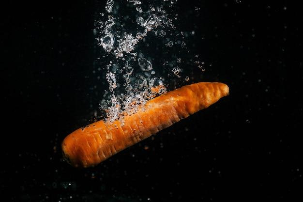 Длинная оранжевая морковь падает в воду