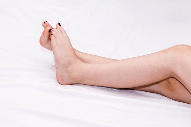 白いベッドの長い完璧な女性の足