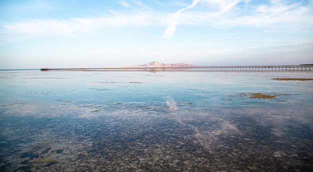 Long pier among the sea and mountains. the sky is reflected in the water.