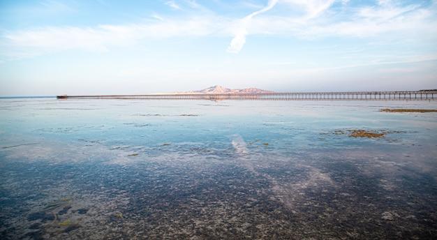 바다와 산 사이의 긴 부두. 하늘이 물에 비친다.