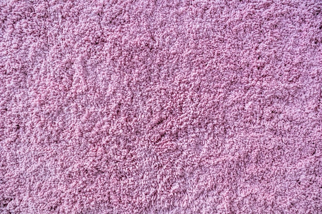 Long pile carpet texture abstract background of shaggy pink fibers