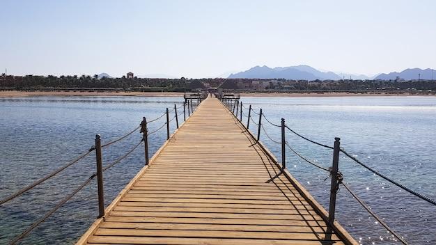 Длинный понтон на берегу красного моря в египте. понтон для спуска в воду. деревянный мост на территории отеля amway в шарм-эль-шейхе с металлическими ограждениями и канатом через море с волнами.