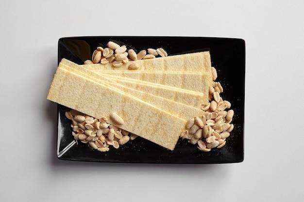 長いポテトチップス、ローストした皮をむいたピーナッツ、白いテーブルの上のプレートの塩味のビールスナック、上面図
