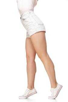 コピースペースで白い壁に分離された長いきれいな女性の脚。デザインの準備ができました。スポーティーでフィット感のあるフィギュア、ファッション、ビューティーのコンセプト。