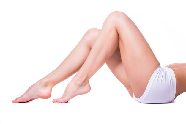 Gambe lunghe e graziose della donna isolate su priorità bassa bianca