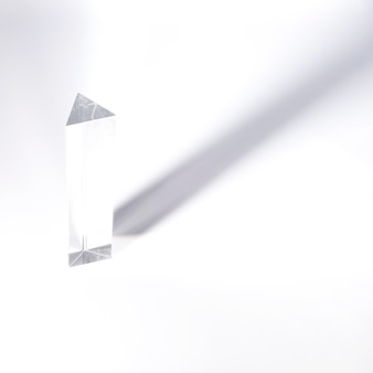 Long prism crystal with dark shadow on white backdrop