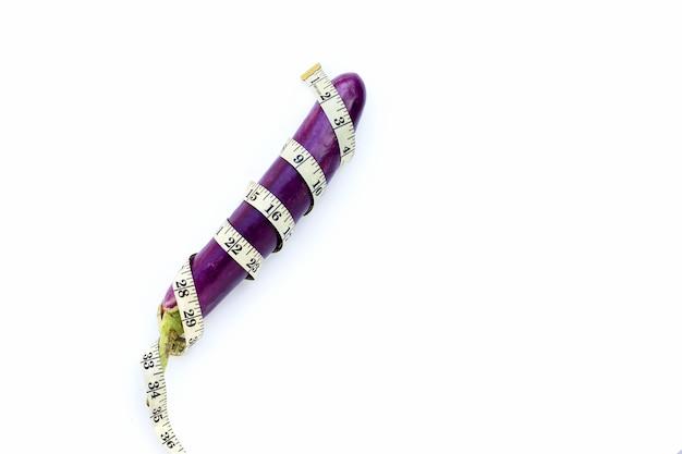 Длинные фиолетовые баклажаны, завернутые в измерительную ленту на белом фоне.