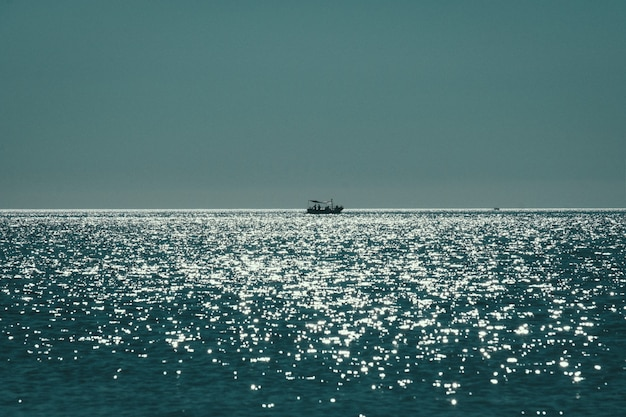 Long range shot of a boat sailing on the sea reflecting the sun