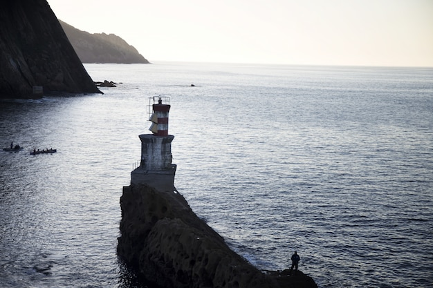 Long-range shot of a lighthouse on a cliff in the sea with people beside it
