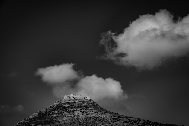 Long range shot of a mountain with houses on top in black and white