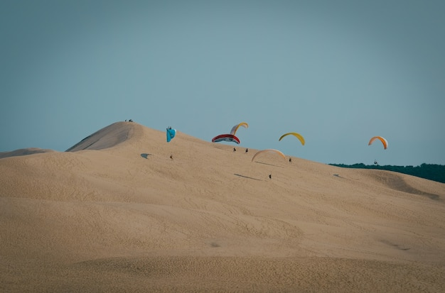 Long-range shot of paragliders landing on a sand dune with clear blue sky