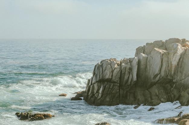 Long-range shot of sea waves hitting the cliff
