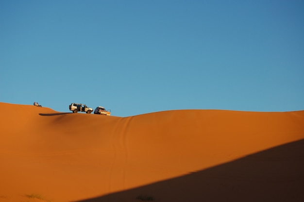 Long-range shot of two cars parked on top of the sand dunes with clear blue sky on a sunny day