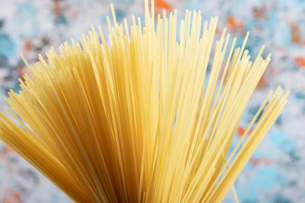 Long raw spaghetti on colorful.