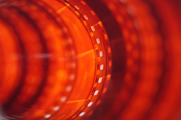 Long red orange photographic film strip closeup background 35 mm film