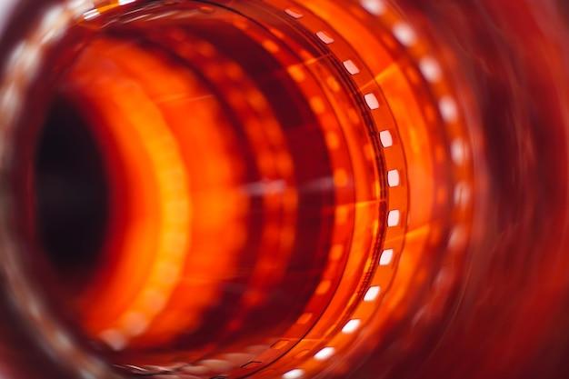 長い赤オレンジ色の写真フィルムストリップのクローズアップの背景35mmフィルム