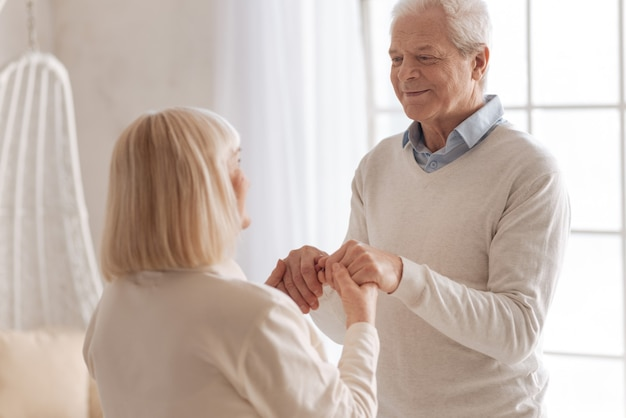 Long relationships. delighted nice aged man holding hands of his wife and smiling while being with her