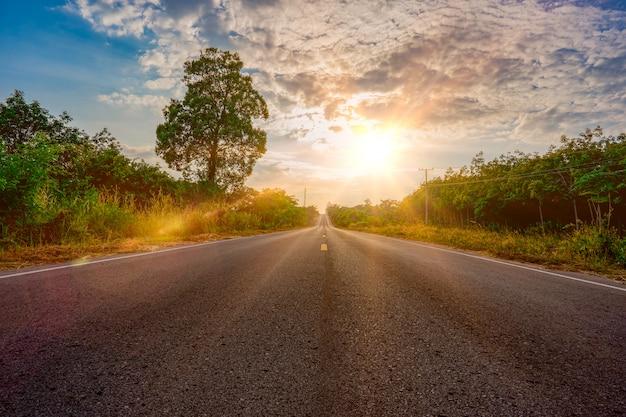 日の出の朝に長い道の通り