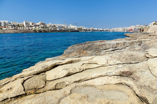 A long rocky coast opposite to the beautiful historical city which are separated by the blue water of the sea.