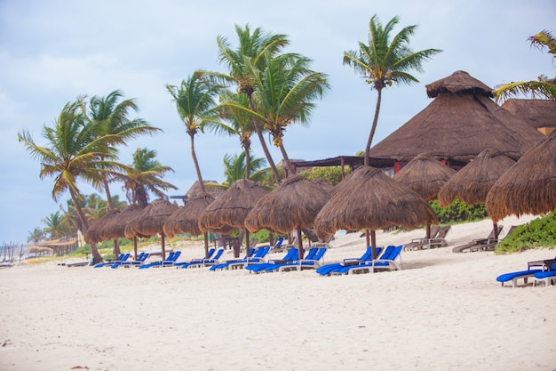 Long row of beach blue deck chairs with umbrellas on white tropical plage