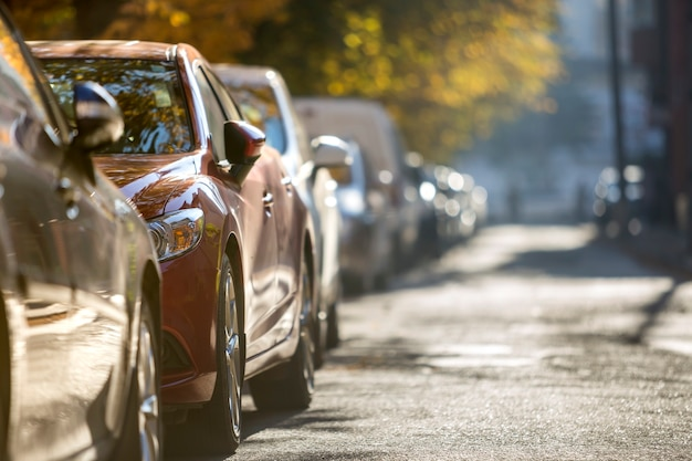 Long row of different shiny cars and vans parked along empty roadside on sunny autumn day on blurred green golden foliage bokeh background.