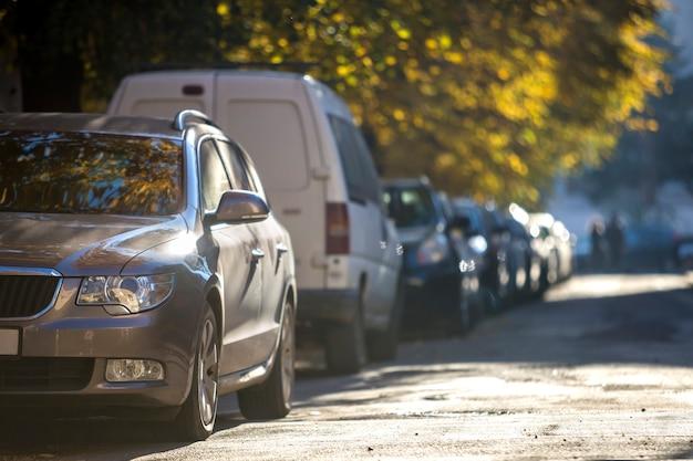 Длинный ряд автомобилей, припаркованных вдоль дороги в солнечный осенний день на размытом фоне боке зеленой золотой листвы. транспорт, современный городской образ жизни, концепция проблем с парковкой транспортных средств.