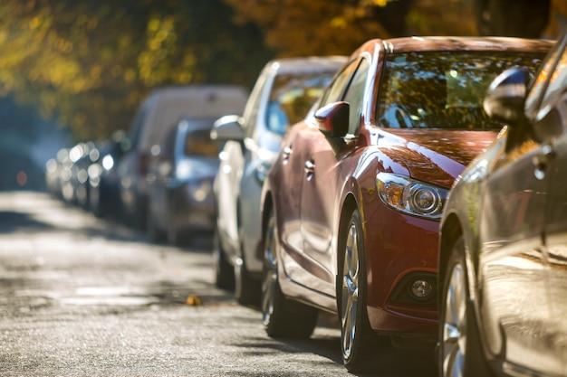 다른 빛나는 자동차와 밴의 긴 행은 화창한가 날에 빈 길가를 따라 주차되었습니다. 현대 도시 생활, 차량 주차 문제 개념.