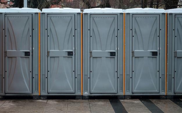 도시 밖에있는 긴 줄의 이동식 바이오 화장실.