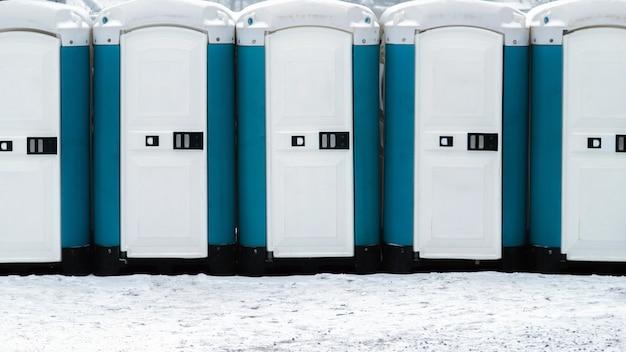 눈 덮인 땅 위에 긴 줄의 이동식 화장실이 있습니다. 야외 바이오 화장실.